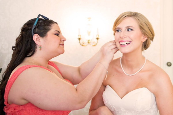 bridesmaid helping bride with an earring