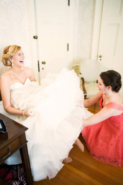 bridesmaid helping bride with garter