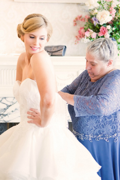 mother of bride zipping bride into dress